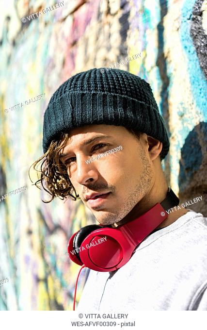 Portrait of young man with red headphones wearing wool cap