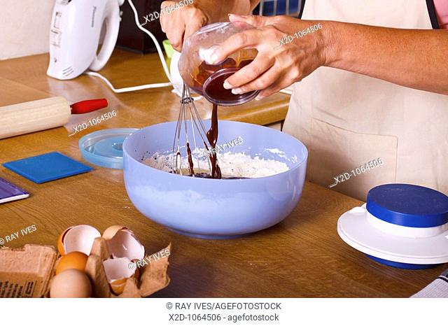 Woman adding cocoa to chocolate cake ingredients in a mixing bowl