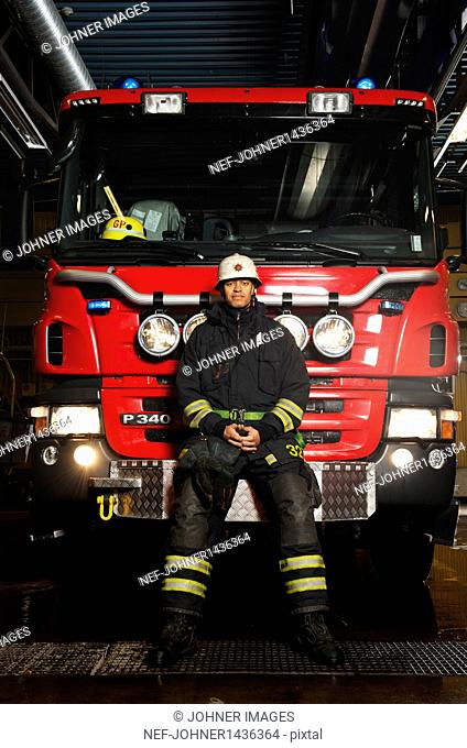 Portrait of fire fighter in front of fire engine