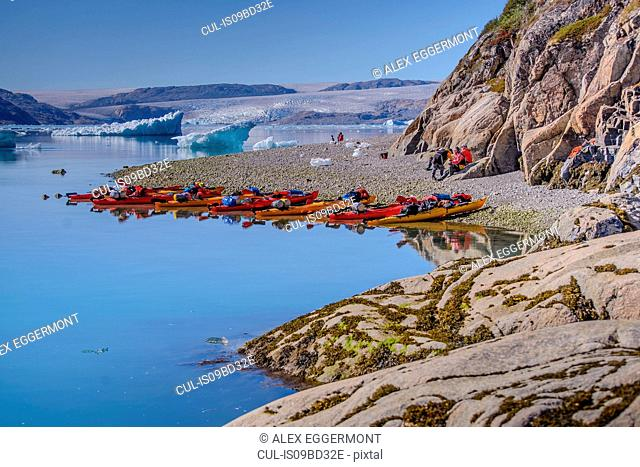 Adventure tourists on fjord beach with rows of kayaks, Narsaq, Vestgronland, South Greenland