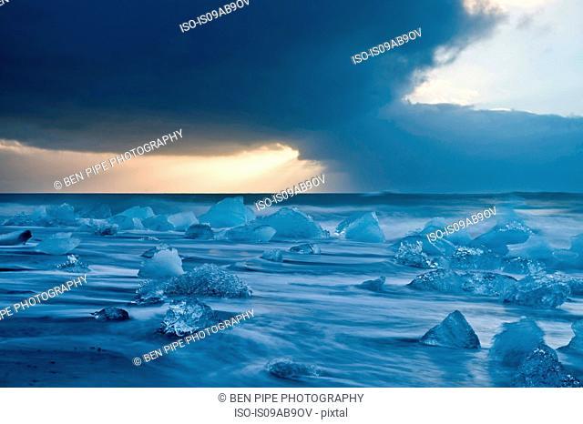Icebergs on beach with stormy sky, Jokulsarlon, Iceland