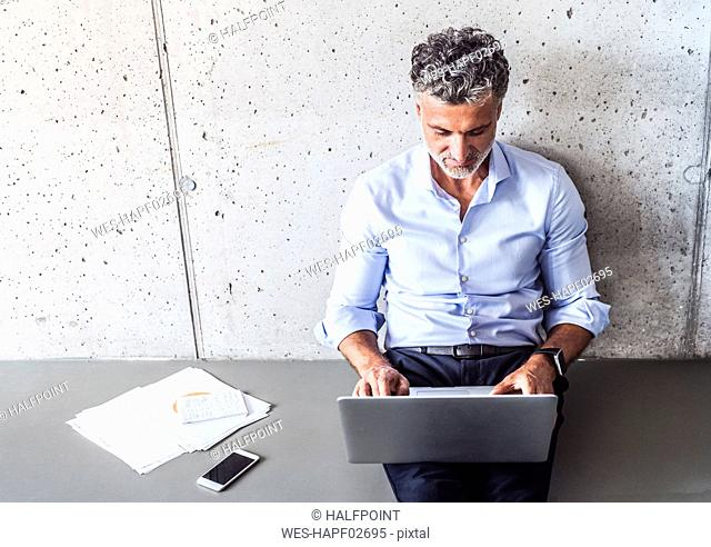 Mature businessman sitting on the floor using laptop