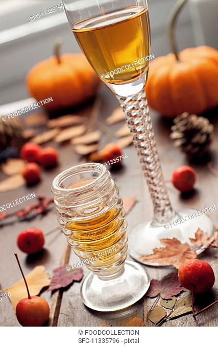 Two glasses of dessert wine with autumnal leaves and berries on a wooden table