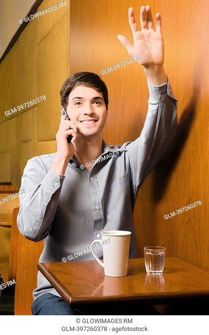 Young man talking on a mobile phone in a cafe