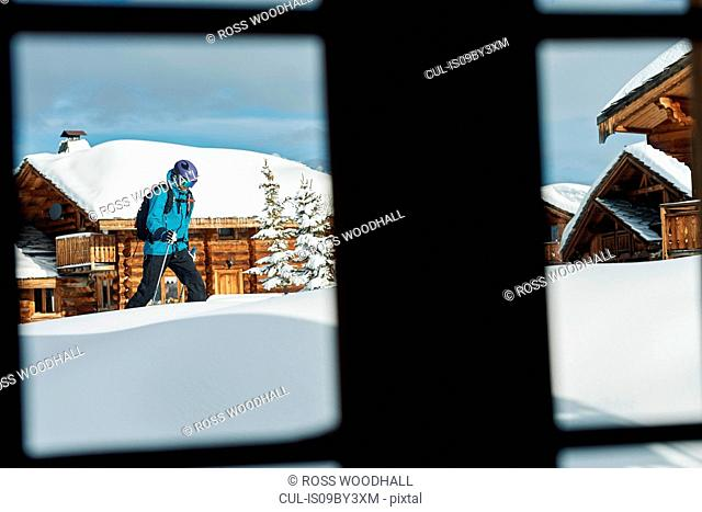 Window view of male skier walking through deep snow near log cabins, Alpe-d'Huez, Rhone-Alpes, France