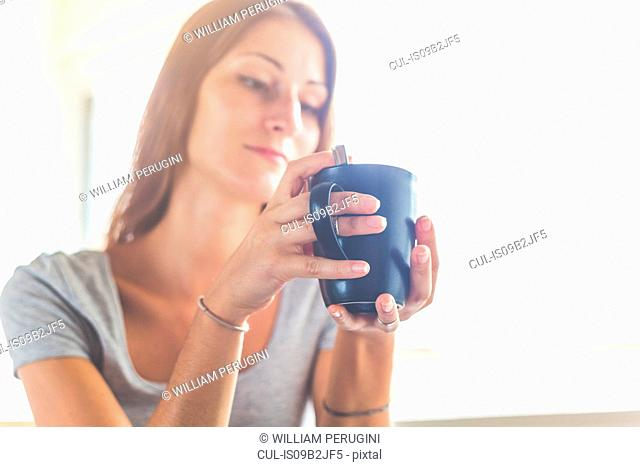 Woman holding cup looking away