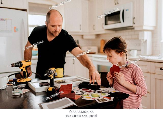 Girl helping father arrange cards into box in kitchen
