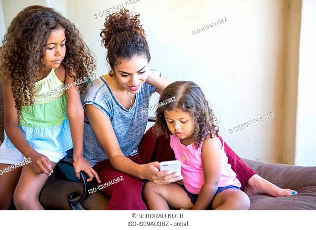 Mother and daughters sitting using smartphone looking down smiling
