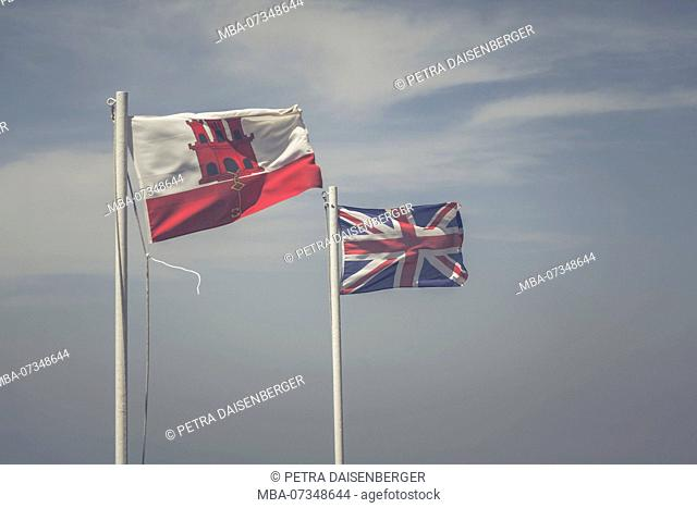 Two flags, the Union Jack and the flag of Gibraltar, blowing side by side in the wind against a blue sky