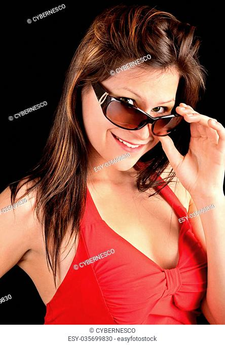 Close-up of a young lady in a red dress looking over her sunglasses