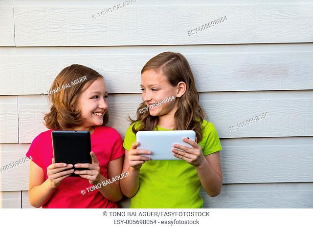 Twin sister girls playing with tablet pc happy on white wall looking each other