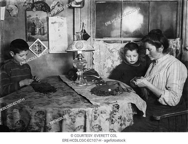 Late at night, sewing tapes on gloves. The boy helps. Family of five sleep in room where the work is done, New York, photograph by Lewis Wickes Hine