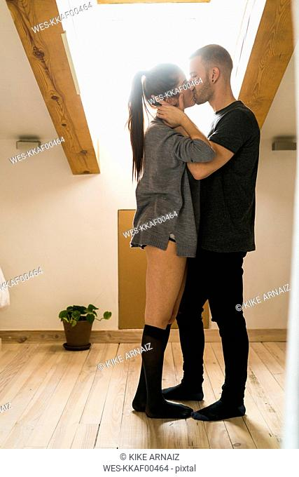 Amorous couple standing at home, kissing and ambracing passionately