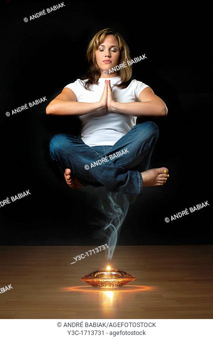 Genie levitation - woman floating in air over smoking oil lamp