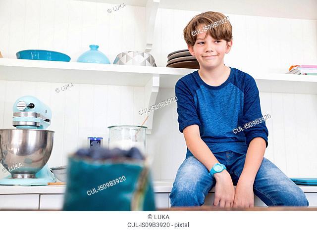 Boy sitting on kitchen work surface