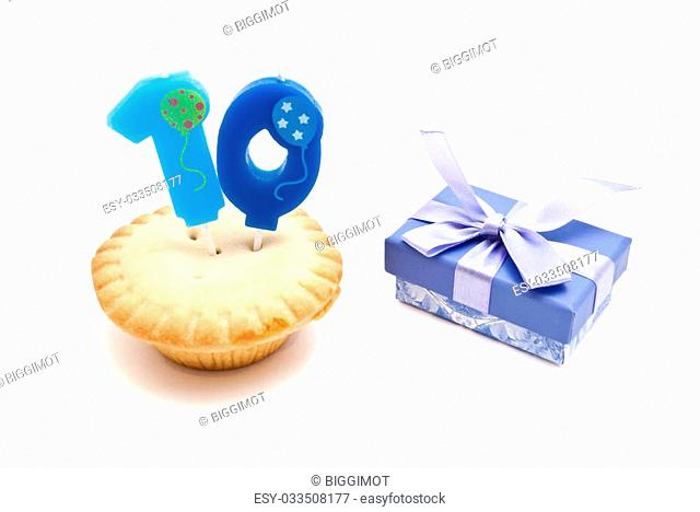 cupcake with ten years birthday candle and gift on white background