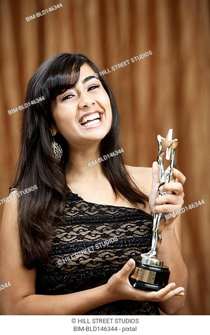 Laughing Filipino teenage girl holding trophy