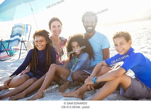 Portrait smiling multi-ethnic family on sunny summer beach