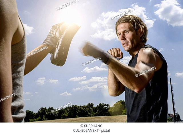 Male boxer training with personal trainer in park