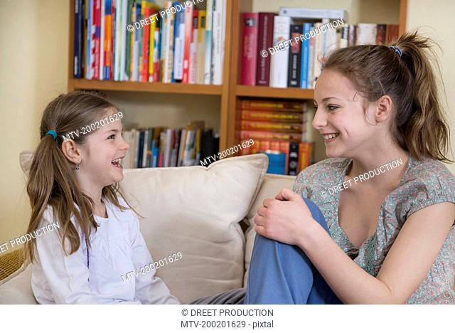 Sisters sitting on couch in living room, smiling