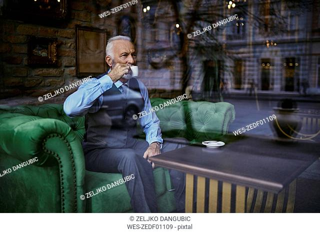 Elegant senior man sitting on couch in a cafe drinking coffee