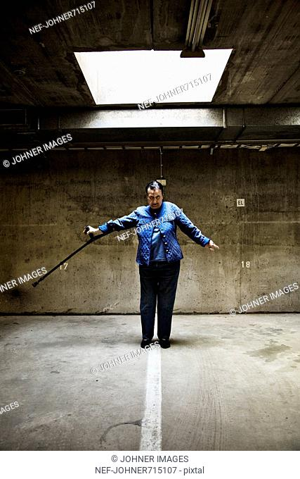 Woman posing with a stick in a garage, Finland