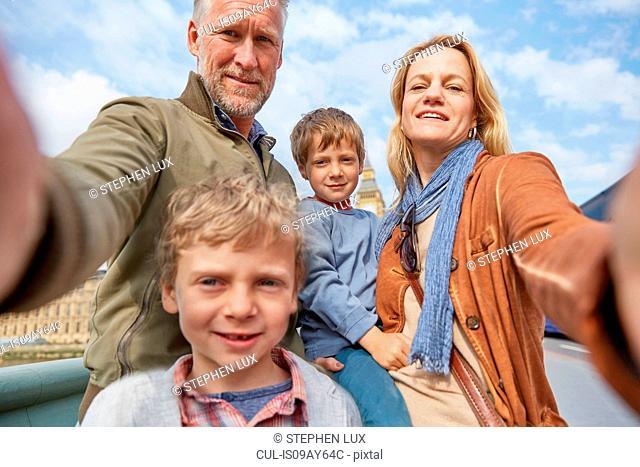 Family taking selfie looking at camera smiling