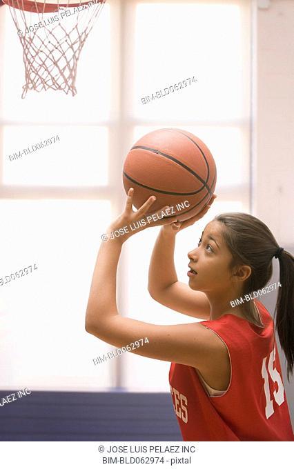 Mixed race girl playing basketball