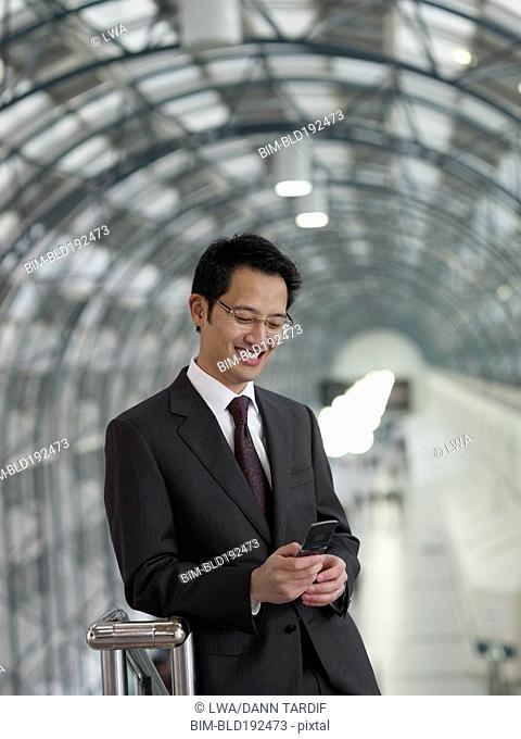 Chinese businessman text messaging on cell phone