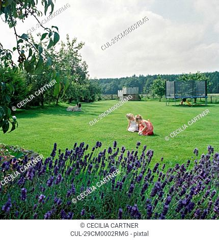 Two girls playing in garden with dog