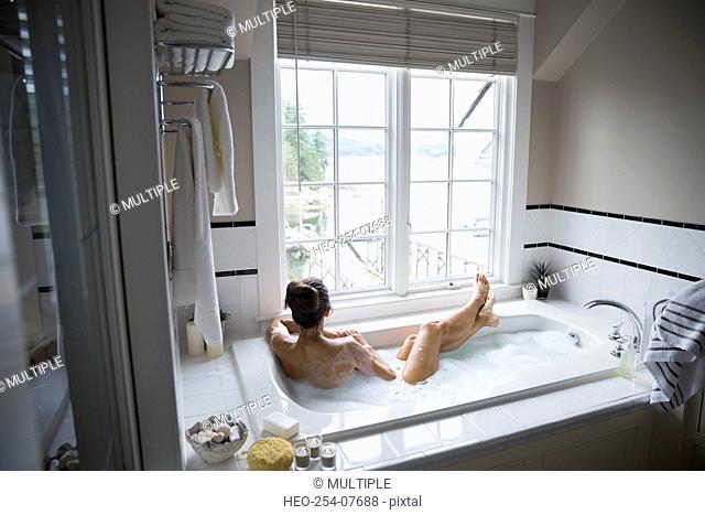 Woman enjoying bubble bath with lake view