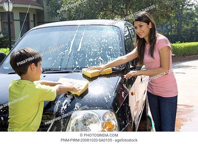 Boy helping his mother washing a car, New Delhi, India