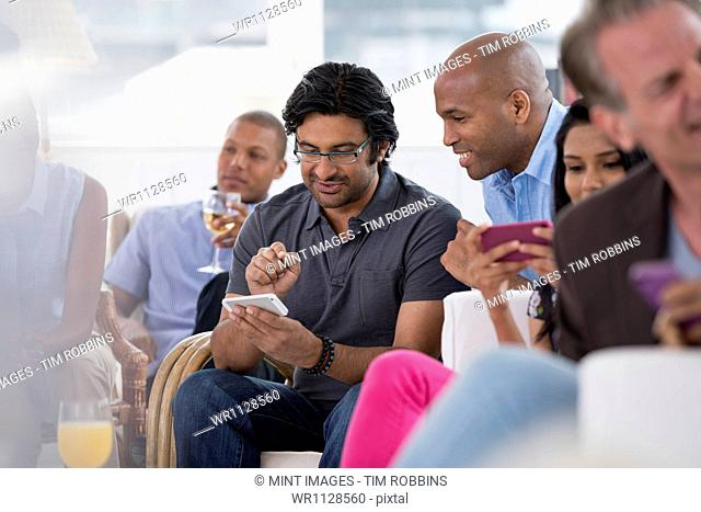 A group of people gathering together for a party or an office event. A woman checking her smart phone