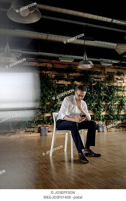 Businessman sitting on chair in green office looking at cell phone