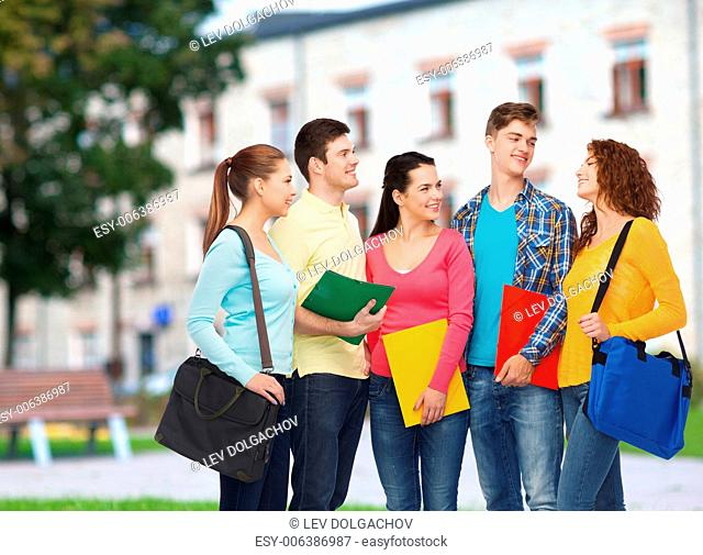 friendship, school, education and people concept - group of smiling teenagers with folders and school bags over campus background