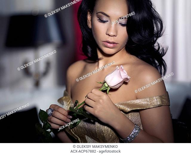 Artistic romantic portrait of a young woman looking at a rose in her hands