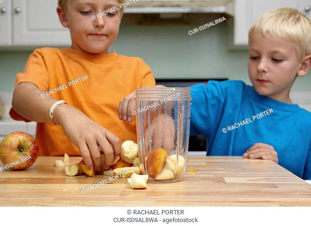 Brothers blending fruits in kitchen