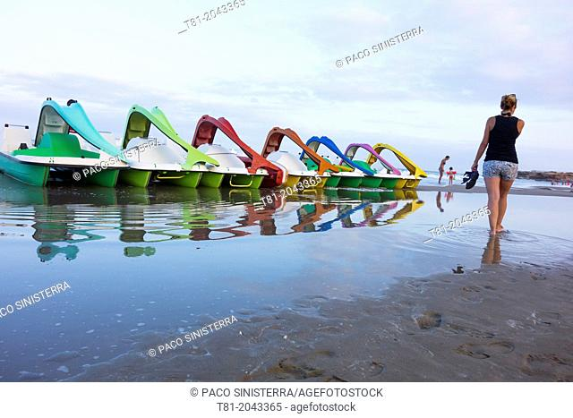 Woman walking on the beach, looking at colourful paddle boats in Almeria, Spain
