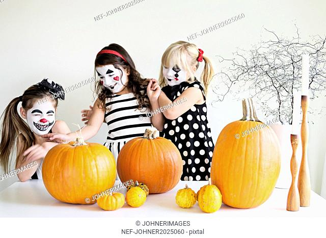 Girl with painted faces playing with pumpkins
