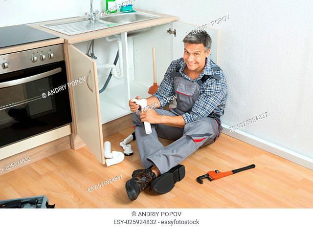 Full length of mature plumber repairing sink pipe in kitchen
