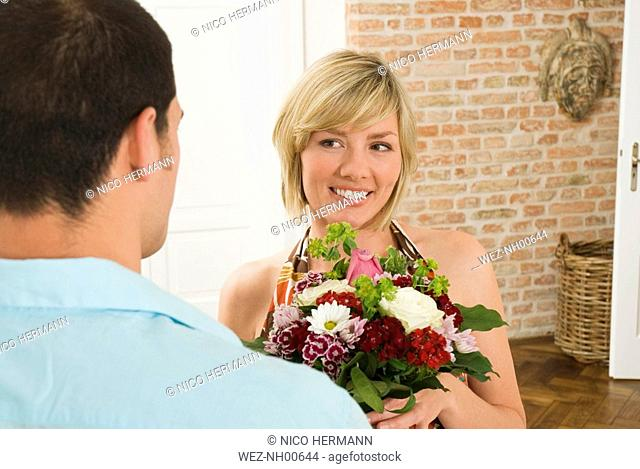 Man giving bunch of flowers to woman, close-up
