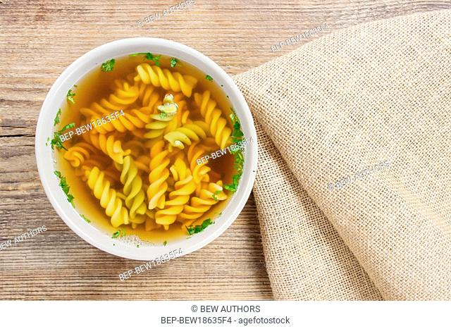 Bowl of chicken soup with noodle on wooden table