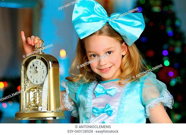 Pretty charming beautiful artistic blond baby girl in Christmas costumes. Beautiful blonde girl with a bow in a blue silk dress