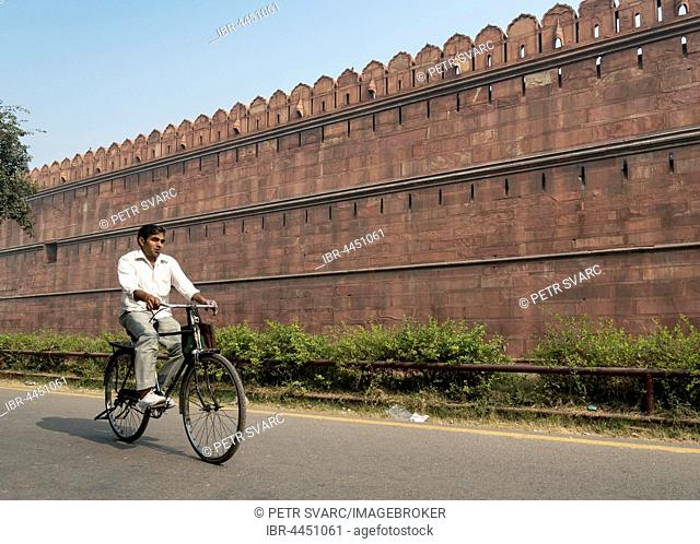 Man on bicycle in front of Red Fort, Old Delhi, Delhi, India
