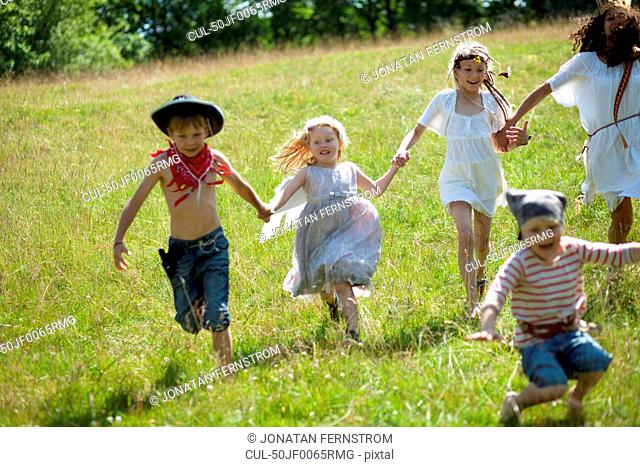 Children in costumes running in field