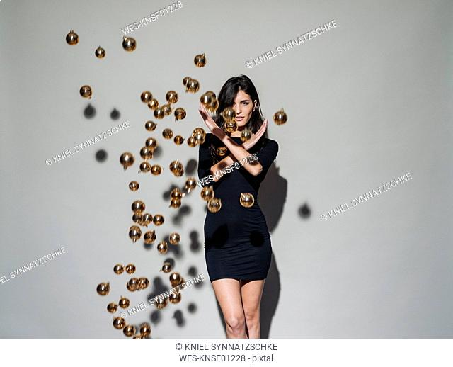 Portrait of young woman surrounded by Christmas baubles floating mid-air