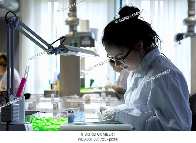 Medical laboratory assistant dissecting samples