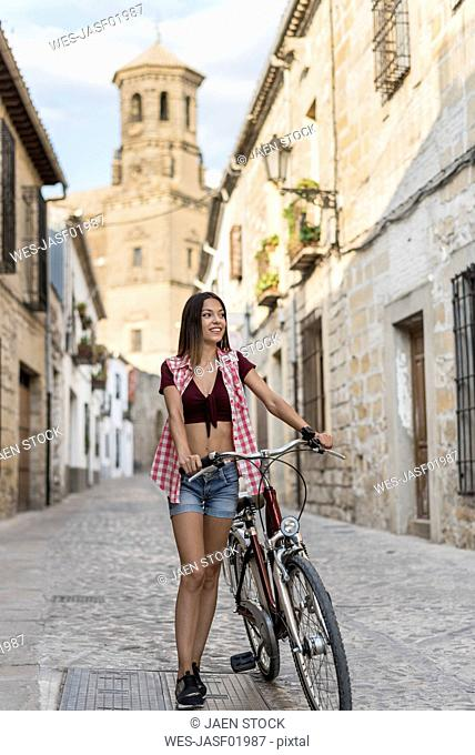 Spain, Baeza, smiling young woman with bicycle in the city