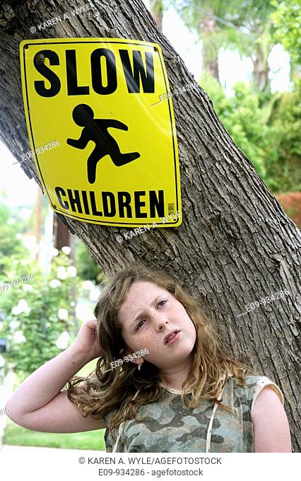 tree trunk with 'Slow Children' sign, girl in front of tree with puzzled expression and body language