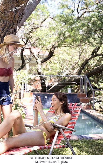 Two young women with cell phone at the poolside